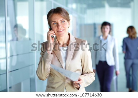 Mature business woman talking over the phone in the corridor of the office building - stock photo