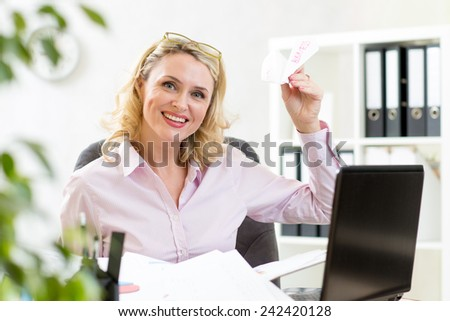 mature business woman throwing paper airplane in office - stock photo