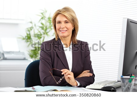 Mature business woman working with computer in the office. - stock photo