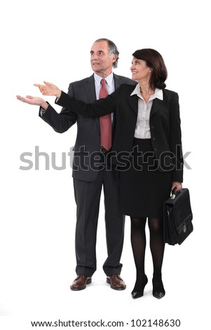Mature businesscouple gesturing at blank copyspace - stock photo