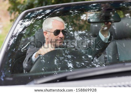 Mature businessman adjusting his cabriolet rear view mirror while driving - stock photo