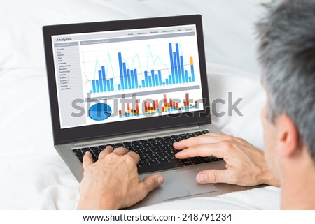Mature Businessman Analyzing Graphs On His Laptop At Home - stock photo