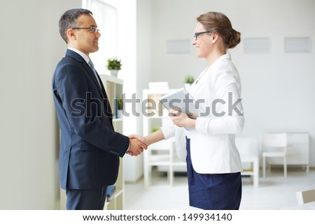 Mature businessman and businesswoman handshaking in office