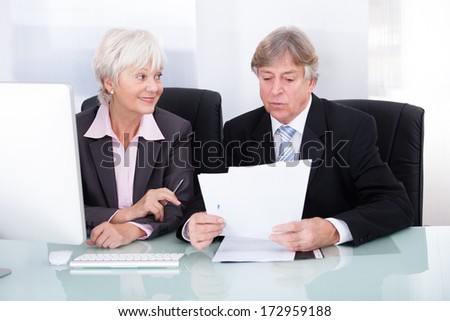 Mature Businessman And Businesswoman Looking At Computer - stock photo