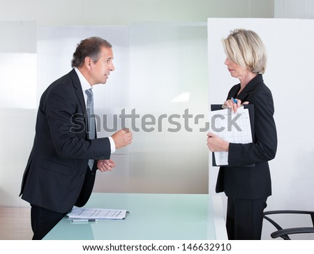 Mature Businessman And Businesswoman Looking At Each Other With Angry - stock photo