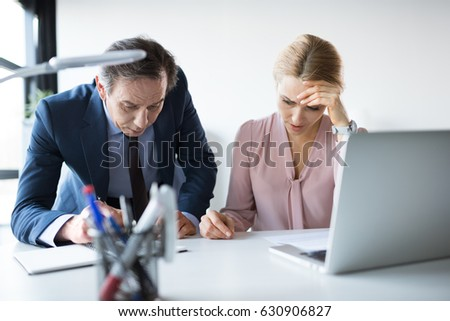 mature businessman and businesswoman with laptop and documents working in office