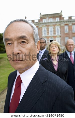 Mature businessman and colleagues by manor house, close-up - stock photo