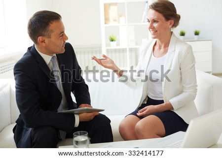 Mature businessman and his colleague discussing working plans in office