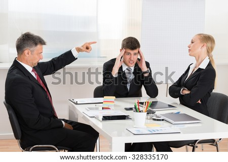 Mature Businessman Arguing With His Two Co-workers In Office - stock photo