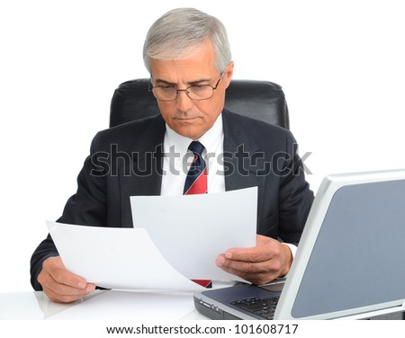 Mature businessman at desk reading papers. Man is wearing eye glasses and has a laptop computer.