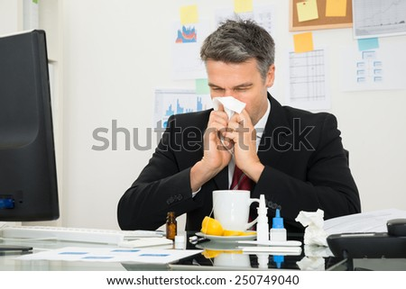 Mature Businessman At Office Desk Blowing His Nose - stock photo