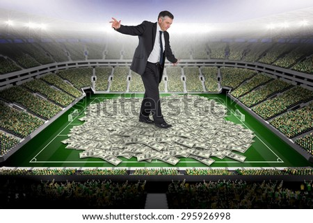 Mature businessman doing a balancing act against pile of dollars - stock photo