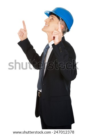Mature businessman engineer with hard hat pointing up. - stock photo