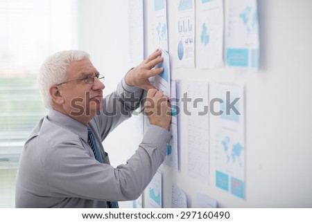 Mature businessman examining reports on the wall - stock photo
