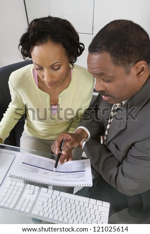 Mature businessman explaining investment plan to woman at office - stock photo