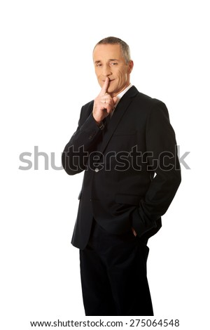 Mature businessman gesturing silent sign. - stock photo
