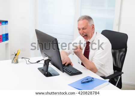 Mature businessman getting angry with his pc - stock photo