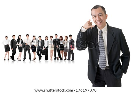 Mature businessman give you a gesture of call and standing in front of his team on studio white background. - stock photo