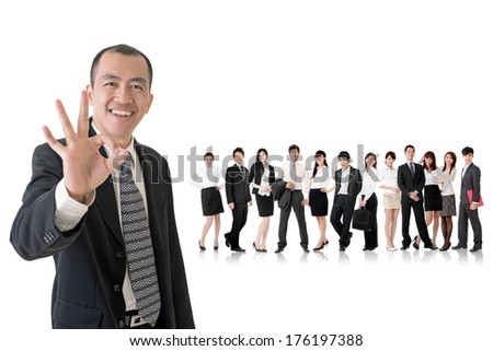 Mature businessman give you a gesture of okay and standing in front of his team on studio white background.