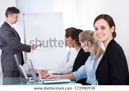 Mature Businessman Giving Presentation To His Colleagues At Office Meeting - stock photo