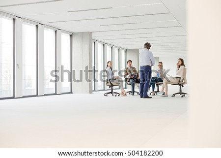 Mature businessman having discussion with colleagues sitting on chair in new office