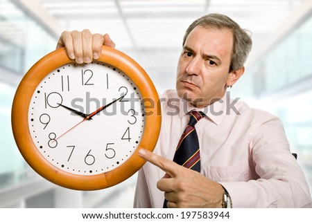 mature businessman holding a clock at the office - stock photo