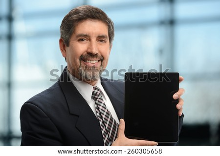 Mature Businessman holding an electronic tablet inside an office building - stock photo