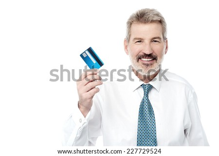 Mature businessman holding out his new credit card