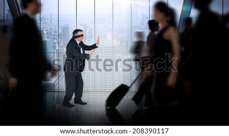 Mature businessman in a blindfold against room with large window looking on city