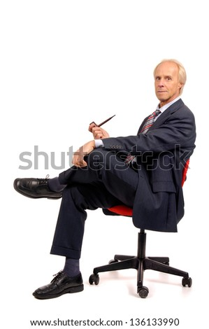 Mature businessman in a chair with a pipe - stock photo