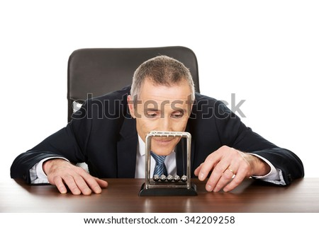 Mature businessman in office playing with newton balls. - stock photo