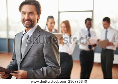 Mature businessman in suit looking at camera with his colleagues working on background - stock photo