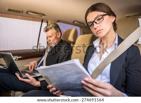 Mature businessman in suit sitting in the car with his beautiful personal assistant and using laptop. - stock photo