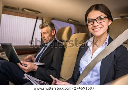 Mature businessman in suit sitting in the car with his beautiful personal assistant and using laptop.