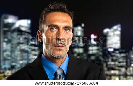 Mature businessman in the city at late night - stock photo