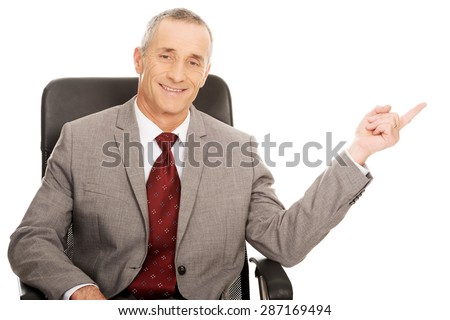 Mature businessman in the office pointing to the left. - stock photo
