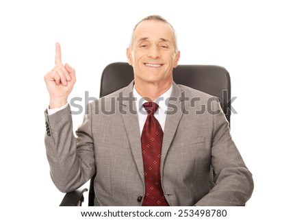 Mature businessman in the office pointing up - stock photo