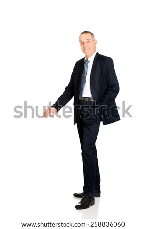 Mature businessman leaning on something invisible - stock photo