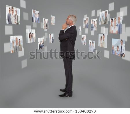 Mature businessman looking at digital interface showing partners