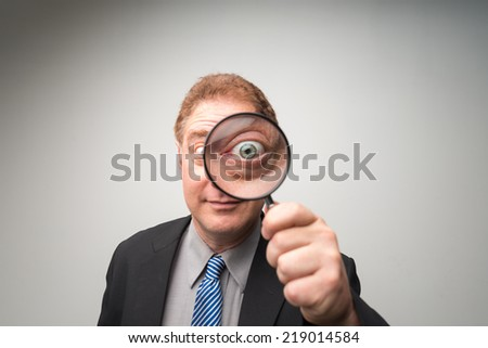 Mature businessman looking through magnifying glass - stock photo