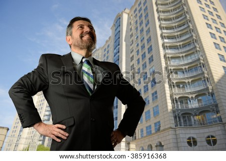 Mature businessman looking up with buildings on the background - stock photo