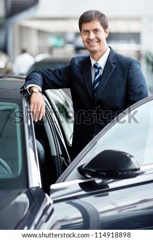 Mature businessman near a car - stock photo
