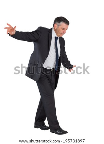 Mature businessman performing a balancing act on white background