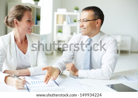 Mature businessman pointing at document and looking at his employee while discussing new strategy in office