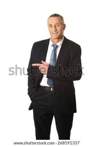 Mature businessman pointing to the left.