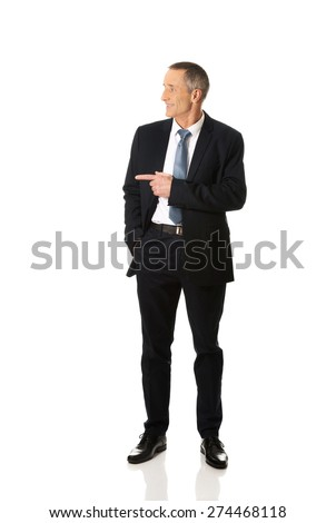 Mature businessman pointing to the left side. - stock photo