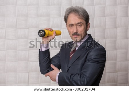 Mature businessman posing with yellow-coloured flashlight in his hand. Serious man is going to clear up the situation connected with low profit. - stock photo
