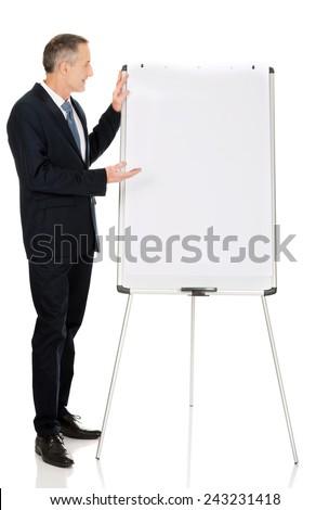 Mature businessman presenting something on flip chart. - stock photo