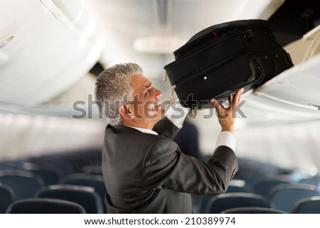 mature businessman putting luggage into overhead locker on airplane - stock photo