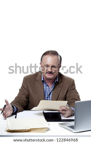mature businessman reading a office document at work